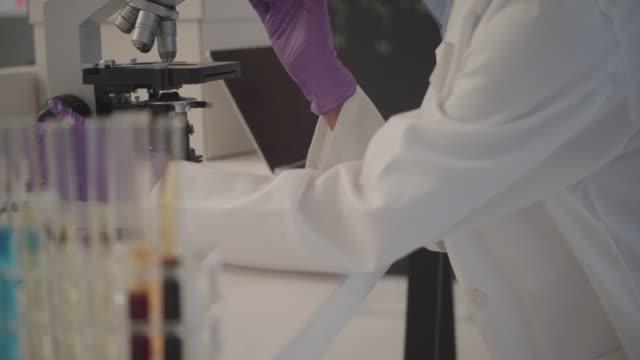Forscher mit Mikroskop In den Lab.