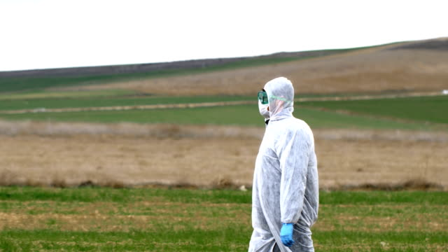 屋外で保護服を着て歩く研究者 - クリーンスーツ点の映像素材/bロール