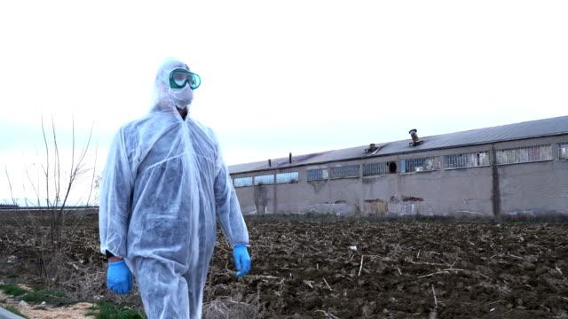 屋外で保護衣装を着た荒廃した地域を歩く研究者 - クリーンスーツ点の映像素材/bロール