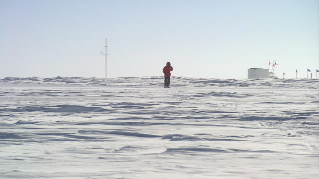 ws researcher walking in the snow as a motorized sled passes / antarctica - antarctica scientist stock videos & royalty-free footage