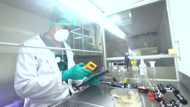 wissenschaftler mit einem mikroskop im labor - elektronik industrie stock-videos und b-roll-filmmaterial