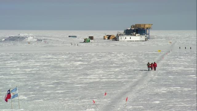 ha researchers walking in snow towards the ceremonial south pole / antarctica - antarctica scientist stock videos & royalty-free footage
