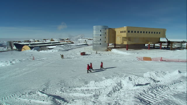 HA Researchers walking in snow towards the geodesic dome / Antarctica
