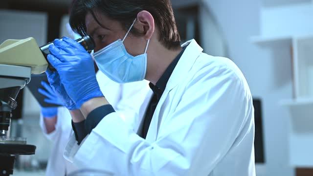 researchers working in a research facility. he looking through a microscope. - 顕微鏡点の映像素材/bロール