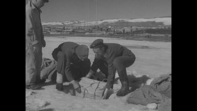 reserve military members carrying crates of dynamite, for use in blasting open an ice jam in the south saskatchewan river; box placed into hole of... - explosive stock videos & royalty-free footage