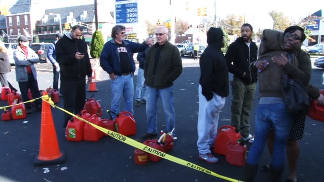 resident line up with gas cans for their home generators in wake of power failure in their suburban neighborhood hurricane sandy aftermath on... - power line点の映像素材/bロール