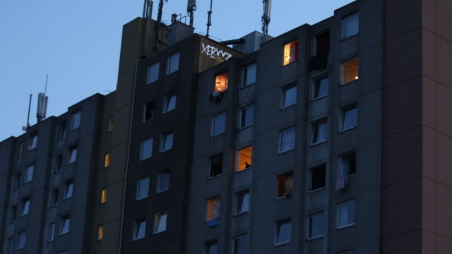 resident of a high-rise apartment building struck by a covid-19 outbreak looks out of an illuminated window at twilight on june 21, 2020 in... - fensterfront stock-videos und b-roll-filmmaterial