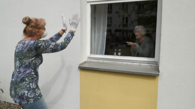 resident waltrud bornschein waves from her room to caregiver marine lehmberg, who is wearing a protective face mask and gloves, while lehmberg was... - community care stock videos & royalty-free footage