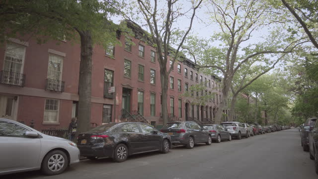 residental brownstone apartment buildings on a street in cobble hill, in brooklyn, new york city on may 11, 2021. - city life stock videos & royalty-free footage