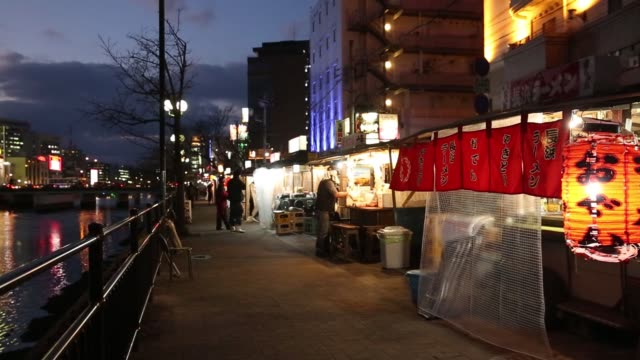 Residential and commercial buildings stand along the Naka River in the Nakasu area of Fukuoka Japan on Dec 21 A vendor prepares to open his yatai...