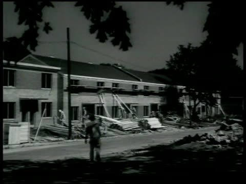residential, apartment complex construction site. carpenters working on site, sawing. bulldozer digging hole near partially completed building .... - 1942点の映像素材/bロール