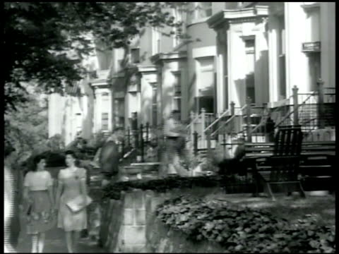 residential block w/ row of brownstones rooming houses woman walking up apartment house steps ringing door bell 'rooms board' sign in window - 1942 stock videos and b-roll footage