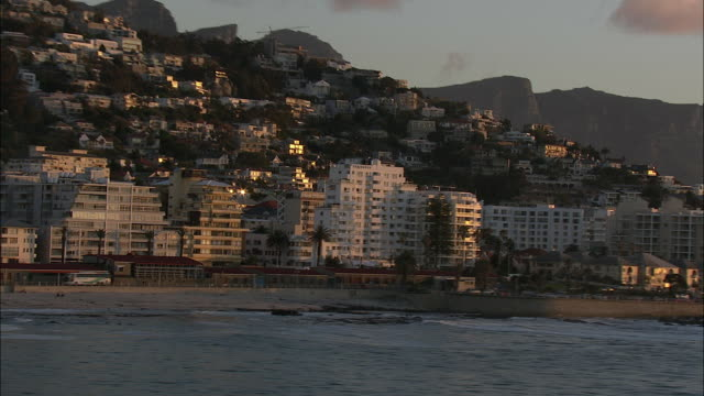 low aerial residential district clifton in evening light with lion's head in background, cape town, western cape, south africa - cape town stock videos & royalty-free footage