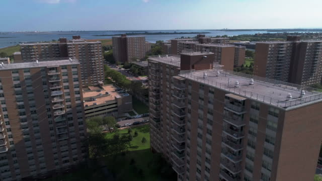"residential district with multi-level social ""projects"" brick buildings in brooklyn, new york, along pennsylvania avenue, with shirley chisholm state park and jamaica bay in the backdrop. aerial drone video with the panoramic-forward camera motion. - housing difficulties stock videos & royalty-free footage"