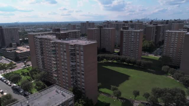 """bostadsområde med multi-level sociala """"projekt"""" tegelbyggnader i brooklyn, new york, längs pennsylvania avenue, med avlägsen utsikt över manhattan. antenn drönare video med framåt kamerarörelse. - kommunalt bostadsområde bildbanksvideor och videomaterial från bakom kulisserna"""