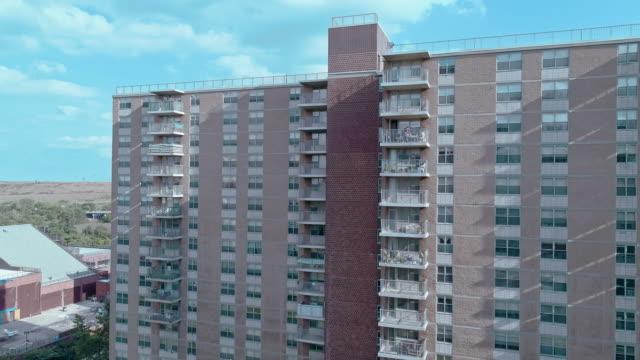 """bostadsområde med multi-level sociala """"projekt"""" tegelbyggnader i brooklyn, new york, längs pennsylvania avenue, med shirley chisholm state park och jamaica bay i bakgrunden. antenn drönare video med stigande kamerarörelse från marken - kommunalt bostadsområde bildbanksvideor och videomaterial från bakom kulisserna"""