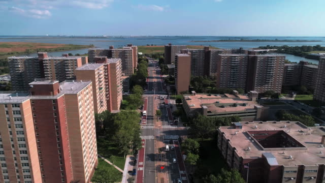 """residential district with multi-level social """"projects"""" brick buildings in brooklyn, new york, with shirley chisholm state park and jamaica bay in the backdrop. aerial drone video with the forward camera motion, along pennsylvania avenue. - brooklyn new york stock videos & royalty-free footage"""