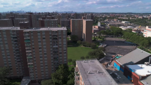 """residential district with multi-level social """"projects"""" brick buildings in brooklyn, new york, along pennsylvania avenue, with the remote view of manhattan. aerial drone video with the forward camera motion. - courtyard stock videos and b-roll footage"""