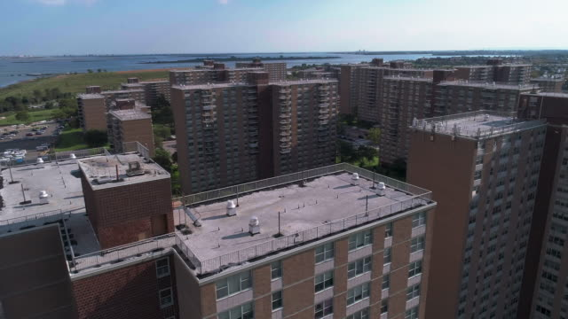 "residential district with multi-level social ""projects"" brick buildings in brooklyn, new york, along pennsylvania avenue, with shirley chisholm state park and jamaica bay in the backdrop. aerial drone video with the forward camera motion. - housing difficulties stock videos & royalty-free footage"