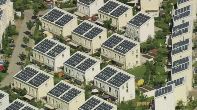 aerial residential housing complex with solar panels on roofs, munich, bavaria - solar panels stock videos & royalty-free footage