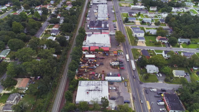 residential neighborhood nearby industrial zone and self-storage hangars in long island, new york state, usa. aerial drone video with the forward and tilting-down camera motion. - self storage stock videos and b-roll footage