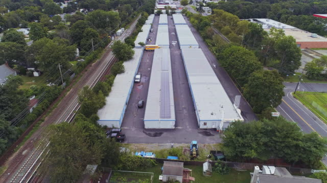 residential neighborhood nearby industrial zone and self-storage hangars in long island, new york state, usa. aerial drone video with the forward camera motion. - self storage stock videos and b-roll footage