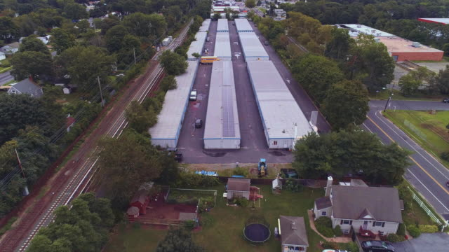 residential neighborhood nearby industrial zone and self-storage hangars in long island, new york state, usa. aerial drone video with the backward camera motion. - self storage stock videos and b-roll footage