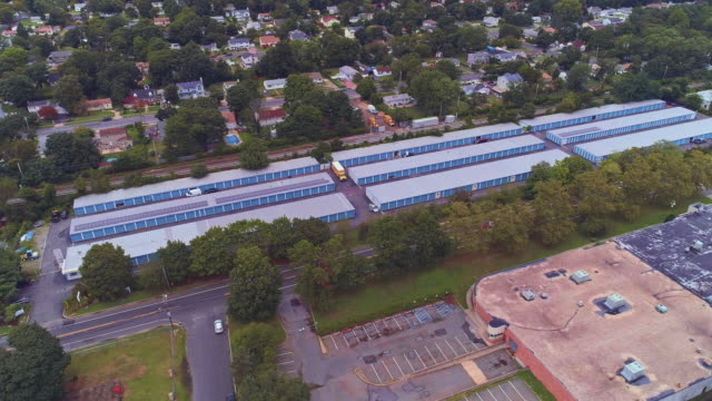 residential neighborhood nearby industrial zone and self-storage hangars in long island, new york state, usa. aerial drone video with the orbit camera motion. - self storage stock videos and b-roll footage