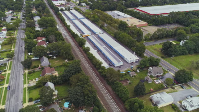 residential neighborhood nearby industrial zone and self-storage hangars in long island, new york state, usa. aссудукфеув hyperlapse-style aerial drone video with the wide-orbit camera motion. - self storage stock videos and b-roll footage