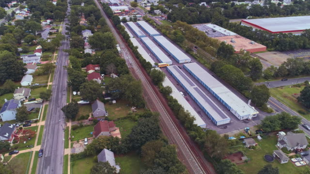 residential neighborhood nearby industrial zone and self-storage hangars in long island, new york state, usa. aerial drone video with the orbit camera motion. - self storage video stock e b–roll