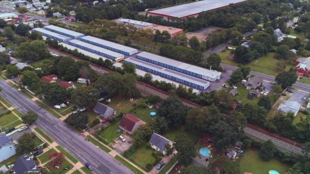 米国ニューヨーク州ロングアイランドの工業地帯とセルフストレージ格納庫に近い住宅街。軌道カメラの動きを伴う空中ドローンビデオ。 - トランクルーム点の映像素材/bロール