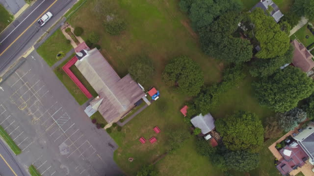 residential neighborhood nearby industrial zone in long island, new york state, usa. aerial top-view, directly-above drone video with the panning camera motion. - self storage stock videos and b-roll footage