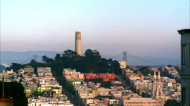 ws, residential neighborhood with coit tower and bay bridge in background, san francisco, california, usa, - north beach san francisco stock videos and b-roll footage