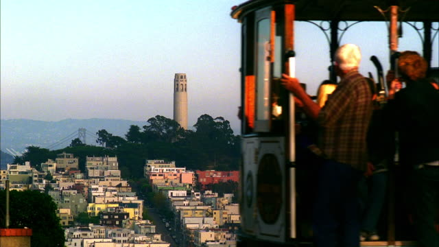 ws, ms, residential neighborhood with coit tower and bay bridge in background, cable car passing in foreground, san francisco, california, usa, - north beach san francisco stock videos and b-roll footage
