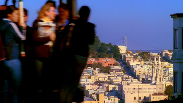 ws, ms, residential neighborhood with coit tower and bay bridge in background, cable car passing in foreground, san francisco, california, usa, - coit tower stock videos & royalty-free footage