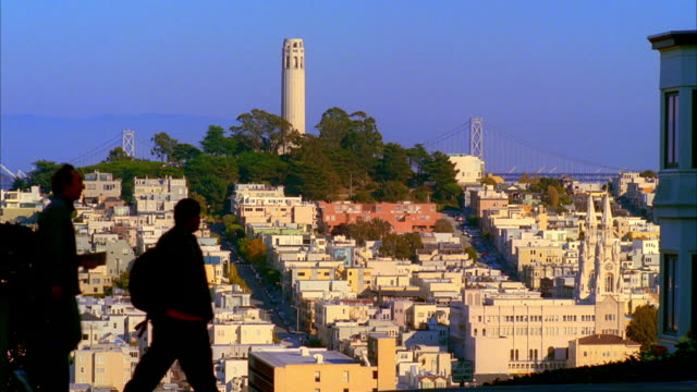 ws, ms, residential neighborhood with coit tower and bay bridge in background, pedestrian and cars passing in foreground, san francisco, california, usa, - north beach san francisco stock videos & royalty-free footage