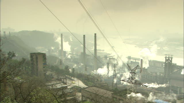 Residential quarter in Chong qing;   Pan to left   factory on the riverbank and rising smoke._Chongqing, Sichuan Province