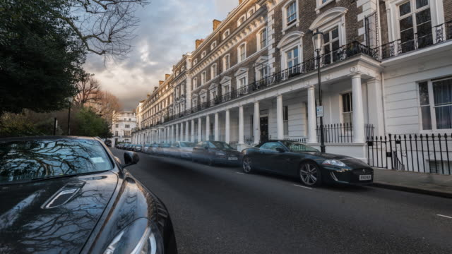 stockvideo's en b-roll-footage met a residential street in south kensington with rapidly moving clouds reflecting in the bodywork of a luxury car parked outside exclusive georgian townhouses - kensington en chelsea