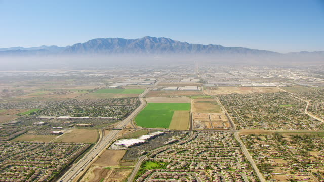 ws aerial pov residential subdivisions shopping malls and cultivated farmland divided by streets and interstate 15 ontario freeway in riverside county with san gabriel mountains in hazy distance / eastvale, california, united states - riverside california stock videos and b-roll footage