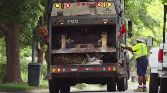Residential trash is compacted by the hydraulic system in a garbage collection truck parked on a neighborhood street.