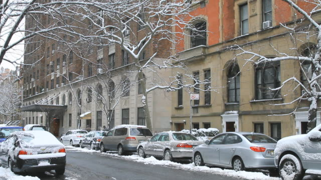 ms residential upper west side street in the snow with building awning and man scraping snow and pedestrian / new york, new york, usa - awning stock videos and b-roll footage
