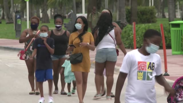 residents and tourists alike wear face masks on miami beach's popular ocean drive as miami-dade county requires face masks in both indoor and outdoor... - miami dade county stock videos & royalty-free footage