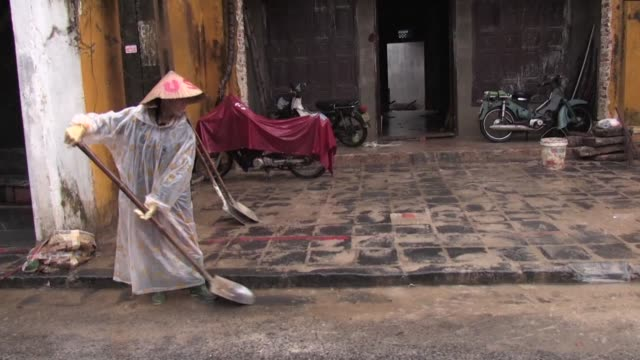 Residents and workers in the city of Hoi An in Vietnam try to clean up damage after typhoon downpours and floods wrought havoc along Vietnam's south...