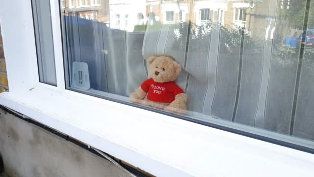 residents display community spirit with art work, teddy bears and smiley faces in windows during the coronavirus pandemic on april 4, 2020 in east... - テディベア点の映像素材/bロール