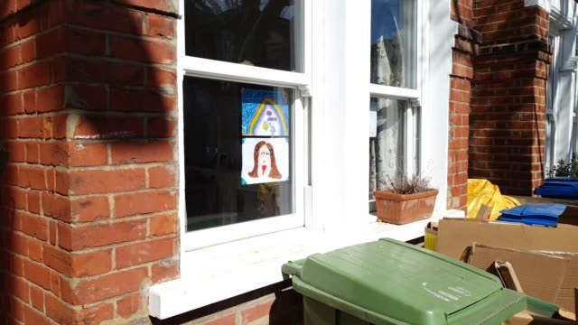 residents display community spirit with art work, teddy bears and smiley faces in windows during the coronavirus pandemic on april 4, 2020 in east... - ぬいぐるみ点の映像素材/bロール