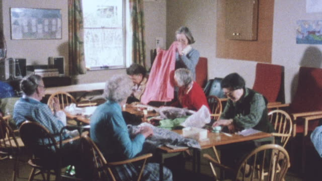 vídeos de stock e filmes b-roll de 1983 ha residents in assisted living center sitting at a table talking, sewing, and working with fabric / united kingdom - costurar