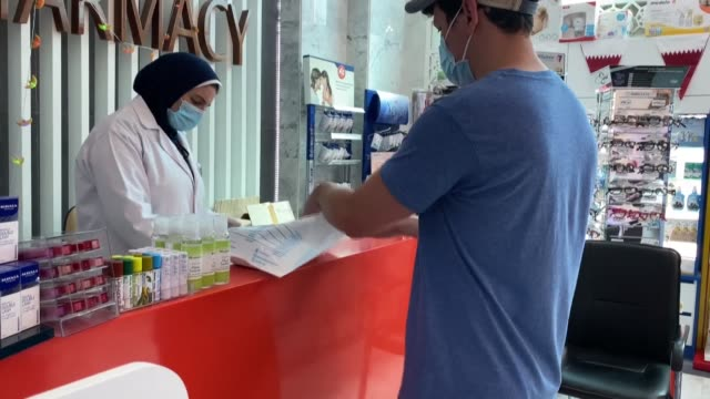 residents in doha head to pharmacies to buy face masks after qatar begins enforcing the world's toughest penalties of up to three years' imprisonment... - qatar stock videos & royalty-free footage