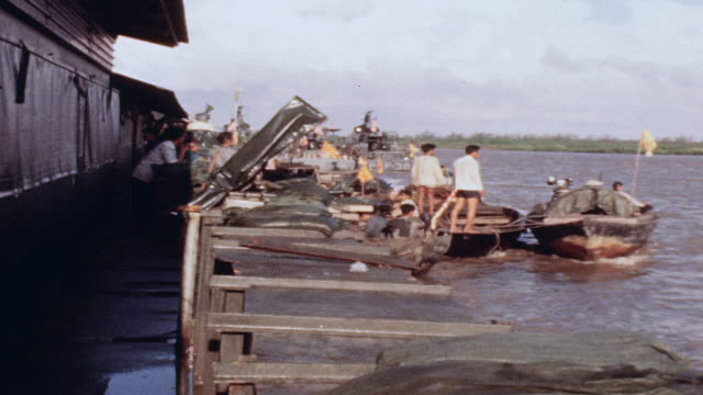 Residents in sampans tying in to mobile river security checkpoint / Vietnam