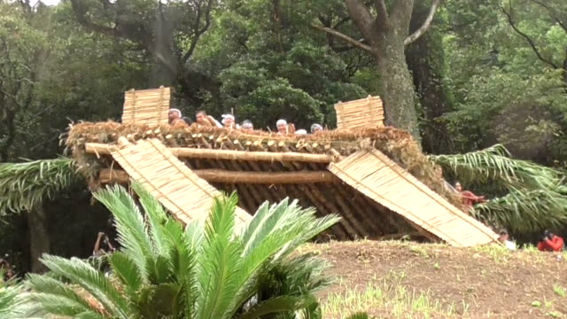 Residents of Akina a village in Tatsugo Kagoshima PrefectureJapan toppled down a straw roof and danced on seaswept rocks during two separate rituals...