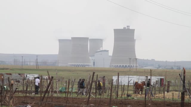 stockvideo's en b-roll-footage met residents of an informal settlement of makeshift homes without electricity or running water walk past fencing near the grootvlei power station... - gauteng provincie